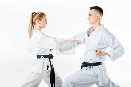 Photo for Side view of karate fighters exercising in kimono isolated on white - Royalty Free Image