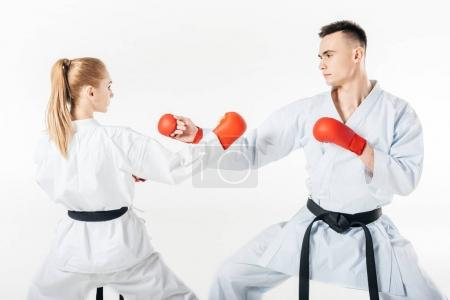 female and male karate fighters with black belts training isolated on white