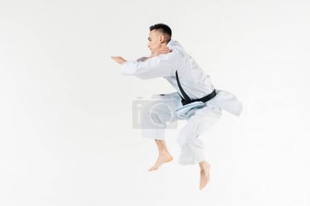 Photo pour Vue latérale du combattant de karaté masculin sautant isolé sur blanc - image libre de droit
