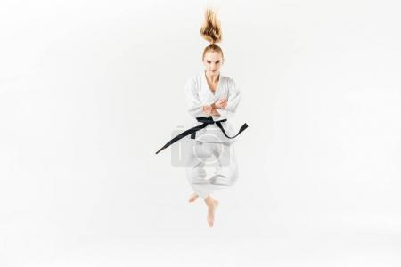 female karate fighter jumping isolated on white