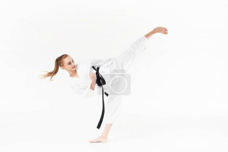 Photo for Female karate fighter with black belt performing kick isolated on white - Royalty Free Image
