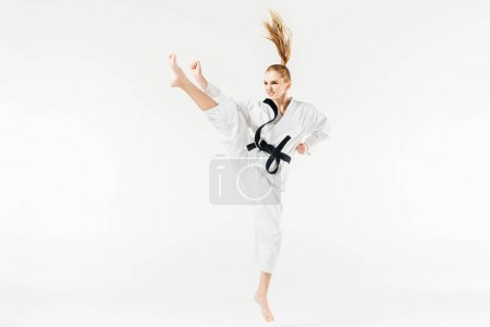female karate fighter performing kick isolated on white
