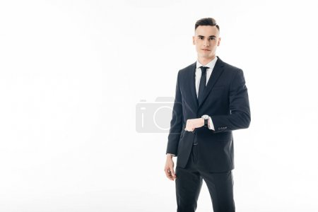 handsome businessman standing with wristwatch isolated on white