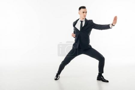 handsome businessman standing in karate position in suit isolated on white