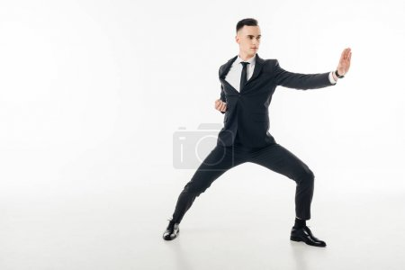 Photo for Handsome businessman standing in karate position in suit isolated on white - Royalty Free Image