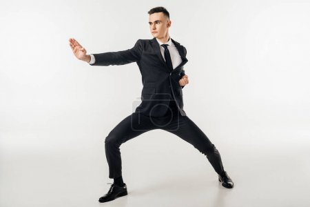 Photo for Businessman standing in karate position in suit isolated on white - Royalty Free Image