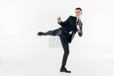 businessman in suit performing karate kick isolated on white