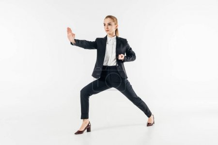 businesswoman exercising karate in suit isolated on white