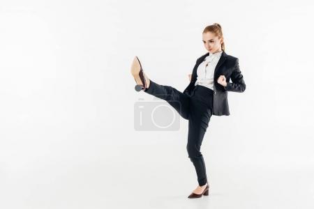 Photo pour Femme d'affaires effectuant karaté coup de pied en costume et talons hauts isolés sur blanc - image libre de droit