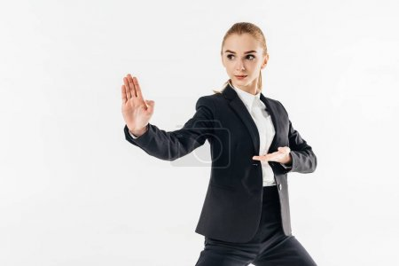 businesswoman in suit standing in karate position and looking away isolated on white