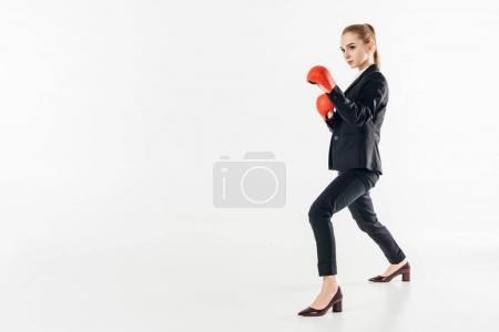 Photo pour Vue latérale de la femme d'affaires en costume et gants rouges isolés sur blanc - image libre de droit