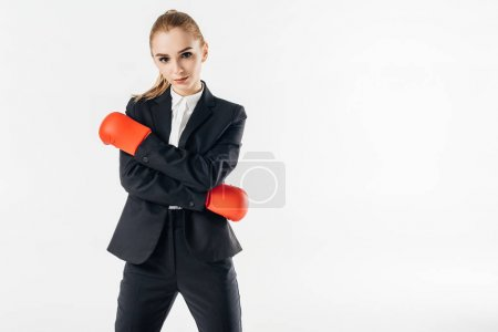 businesswoman standing in suit and red gloves and looking at camera isolated on white