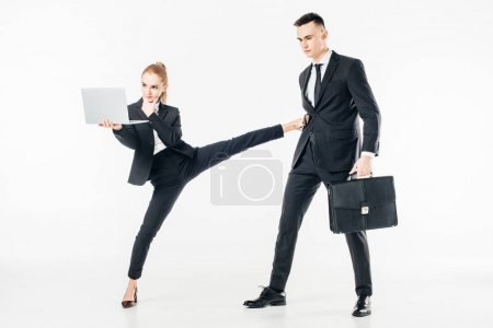 Photo for Businesswoman holding laptop and kicking businessman isolated on white - Royalty Free Image