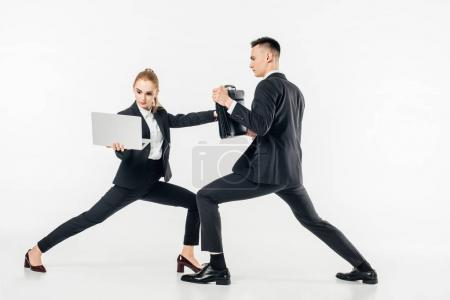 Photo for Businesswoman holding laptop and kicking businessman in bag isolated on white - Royalty Free Image