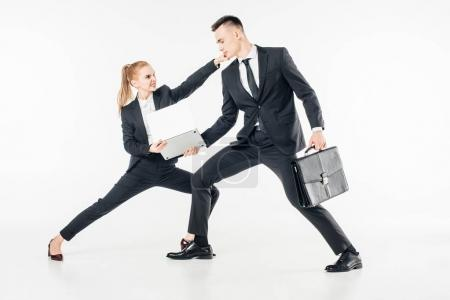 young businesspeople in suits fighting for laptop isolated on white
