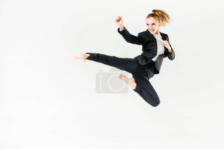 Photo for Businesswoman screaming, jumping and performing kick in suit isolated on white - Royalty Free Image