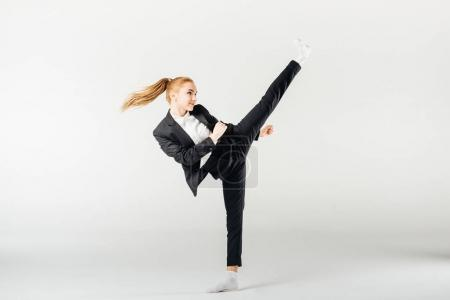 businesswoman performing kick in suit isolated on grey