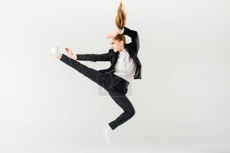 Photo for Female karate fighter jumping and performing kick in suit isolated on grey - Royalty Free Image