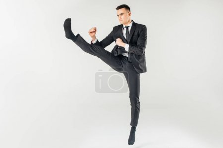 businessman jumping and performing kick in suit isolated on white
