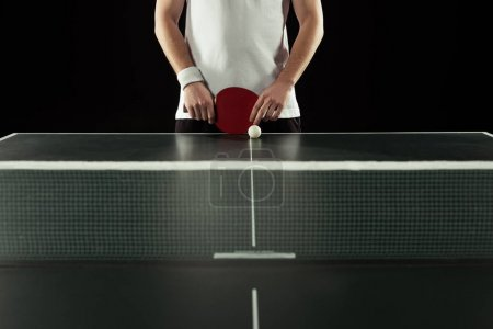 Photo for Partial view of tennis player with racket standing at tennis table isolated on black - Royalty Free Image