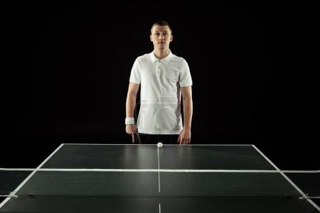 portrait of tennis player in uniform standing at tennis table with ball isolated on black