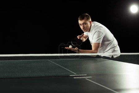 tennis player with tennis racket and ball in hands standing at tennis table isolated on black