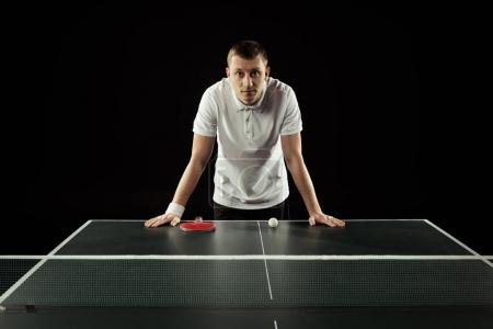 portrait of tennis player leaning on tennis table isolated on black