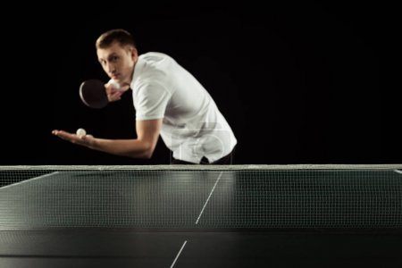 selective focus of tennis player with tennis racket and ball in hands standing at tennis table isolated on black