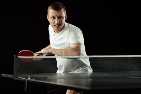 young emotional tennis player in uniform practicing in table tennis isolated on black