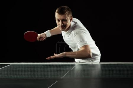young tennis player in uniform practicing in table tennis isolated on black