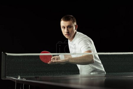 young focused tennis player in uniform practicing in table tennis isolated on black