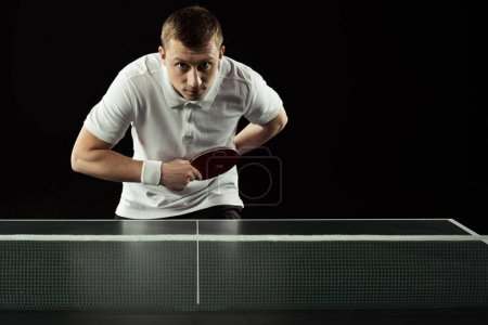 young tennis player playing table tennis isolated on black