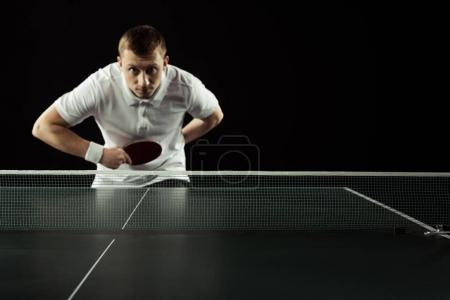 selective focus of young tennis player playing table tennis isolated on black