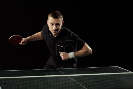 portrait of young tennis player playing table tennis isolated on black