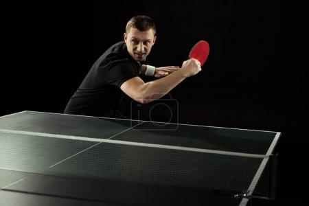 Photo for Portrait of emotional tennis player playing table tennis isolated on black - Royalty Free Image