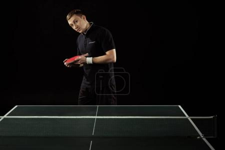 Photo for Portrait of tennis player in uniform with racket standing at tennis table isolated on black - Royalty Free Image