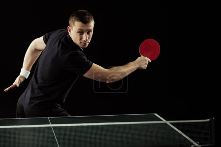 portrait of tennis player in uniform playing table tennis isolated on black