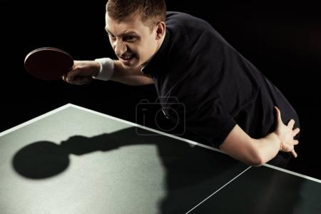angry tennis player in uniform playing table tennis isolated on black