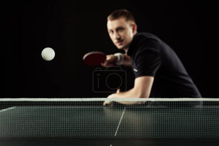 Photo for Selective focus of young tennis player in uniform playing table tennis isolated on black - Royalty Free Image