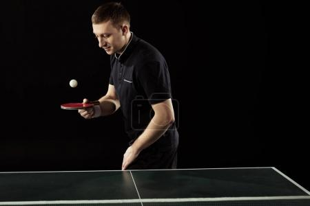 tennis player in uniform practicing with racket and ball isolated on black