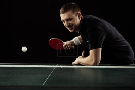 Photo for Smiling tennis player in uniform playing table tennis isolated on black - Royalty Free Image
