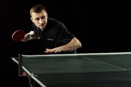 portrait of young tennis player in uniform playing table tennis isolated on black