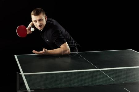 Photo for Focused tennis player playing table tennis isolated on black - Royalty Free Image