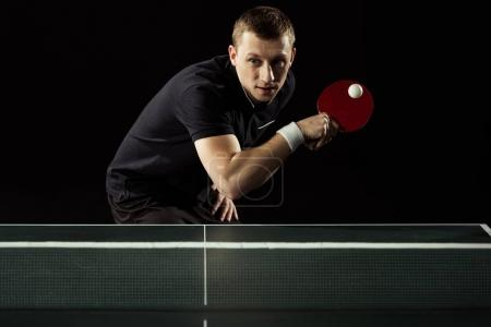 focused tennis player playing table tennis isolated on black