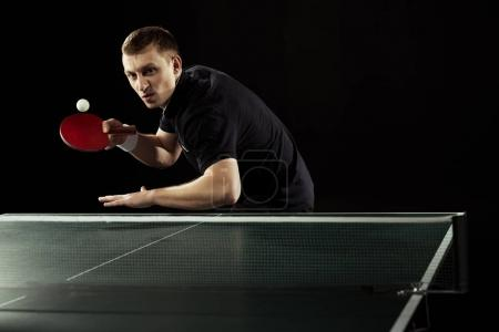 emotional tennis player in uniform playing table tennis isolated on black