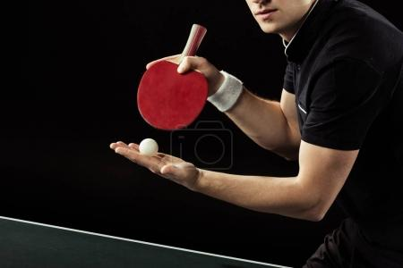 cropped shot of tennis player with tennis ball and racket in hands isolated on black