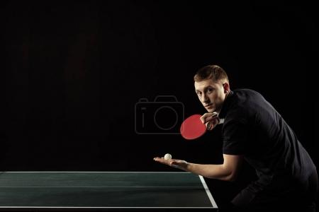 side view of young table tennis player with racket and ball in hands isolated on black