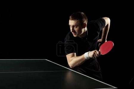 side view of young tennis player practicing in table tennis isolated on black