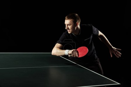 Photo for Side view of young tennis player practicing in table tennis isolated on black - Royalty Free Image