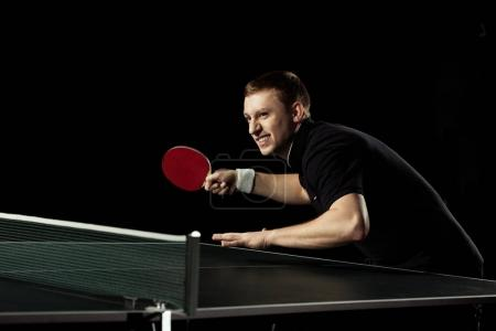 side view of emotional tennis player practicing in table tennis isolated on black
